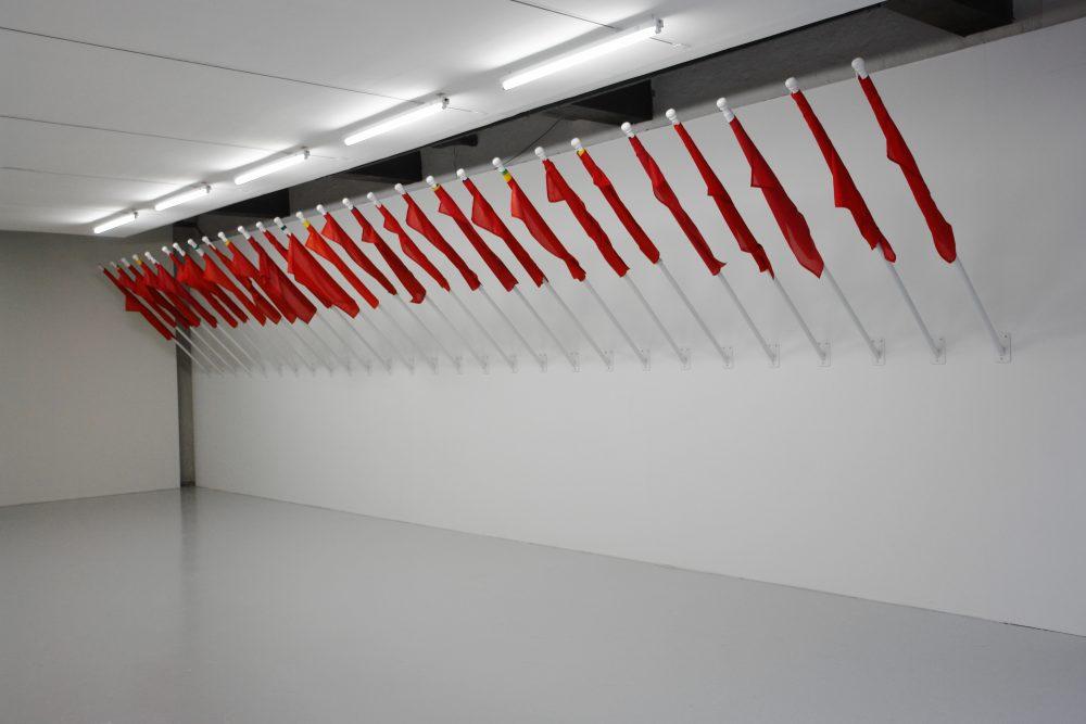 """Fayçal Baghriche — Enveloppements drapeaux de 28 pays, dimensions variables, 2010 Vue de l'exposition """"Quelque chose plutôt que rien"""", Le Quartier, Quimper 2010"""