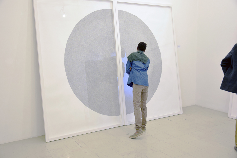 "A viewer looking at 'Circle of Uncertainty (6)'   Zimbabwe Pavilion, at the 57th Venice Biennale 2017  ""Deconstructing Boundaries: Exploring Ideas of Belonging"" curated by Raphael Chikukwa.   Photo: Charles Bhebe, courtesy the National Gallery of Zimbabwe."