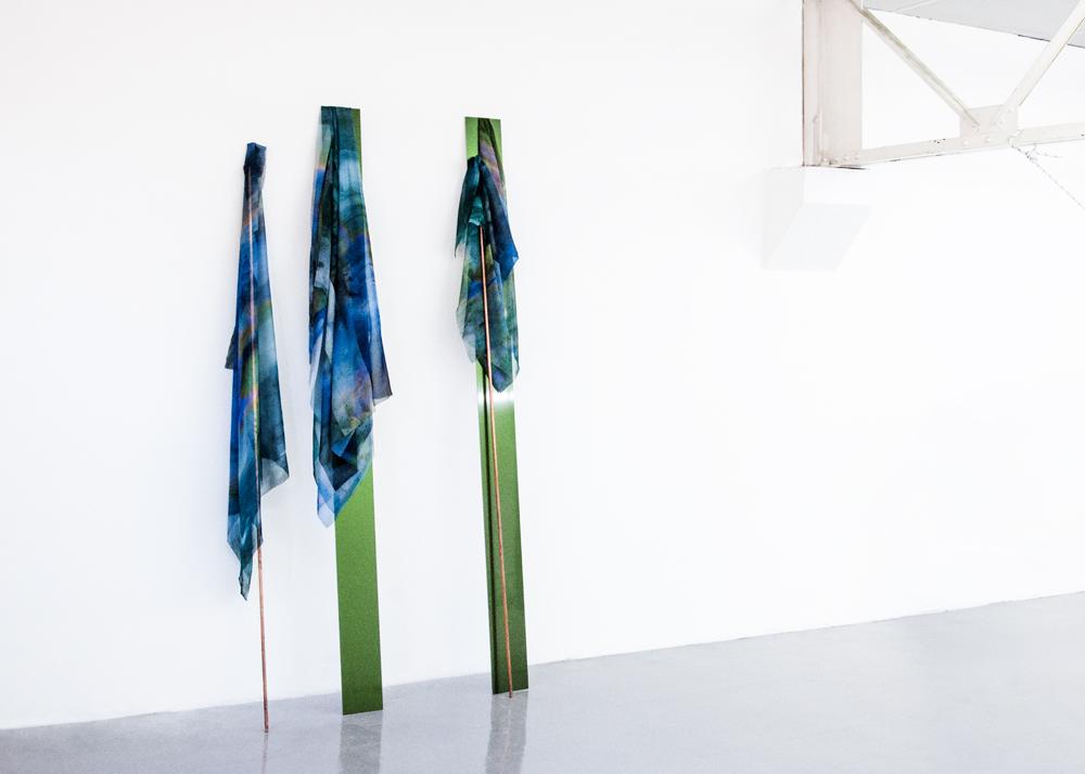 """Laura Rives, """"synarchipel, étandard"""". Impressions textiles par sublimation, alu composite prélaqués, tubes de cuivre 2m20 x 10 cm. Vue d'installation, Lieu-Commun, Toulouse en collaboration avec Julie Kieffer, 2017."""